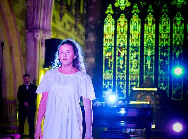 Actor performing in front of stain glass windows at The Hub at St Mary's Lichfield