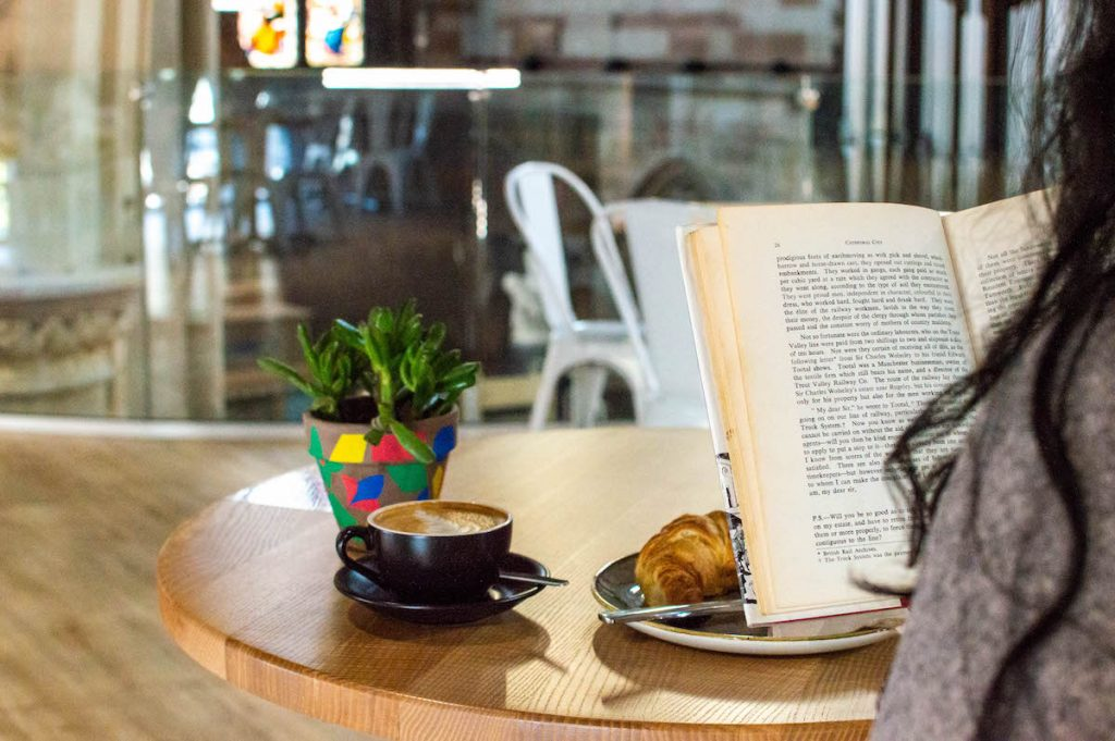 woman enjoying reading a book with a coffee and croissant at The Hub Coffee Shop