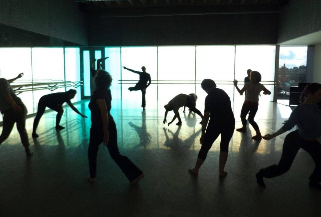 silhouettes of seven dancers moving in different ways in a dance studio