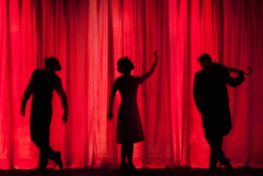 silhouettes of performers on stage against a red curtain